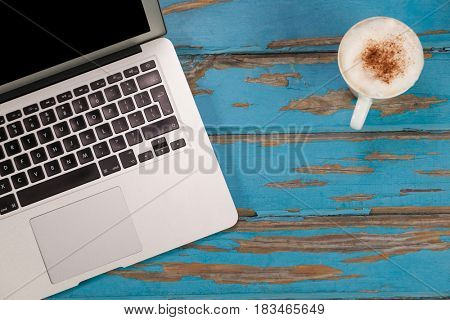 Coffee mug and laptop on old wooden plank