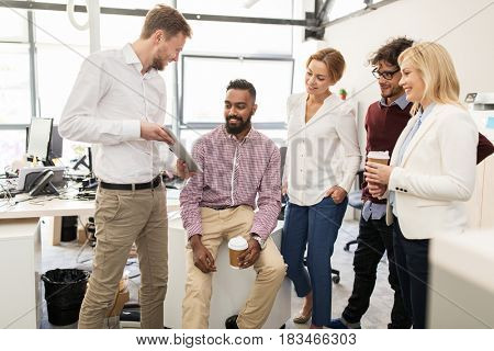 business, technology, break and people concept - happy creative team with tablet pc computer drinking coffee and talking at office