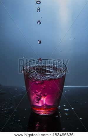 Water drop on the glass and on light background
