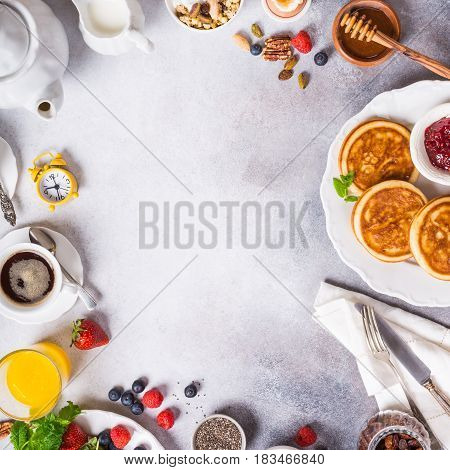 Healthy breakfast background with coffee, pancakes, fresh berries, quick cereals and orange juice, copy space, top view.