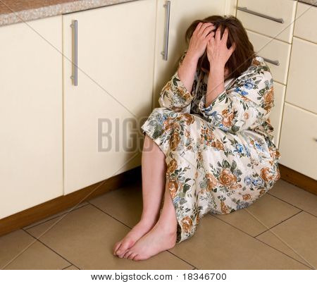 Very sad woman sits on a floor