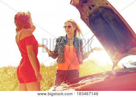 road trip, transport, travel and people concept - young women with open hood of broken car at countryside