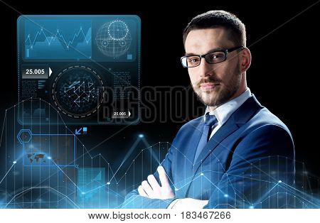 business, people and office concept - businessman in glasses over black background and virtual charts projection