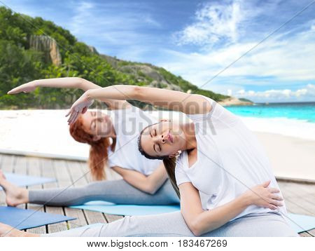 fitness, sport, people and healthy lifestyle concept - women making yoga exercises outdoors over exotic tropical beach background