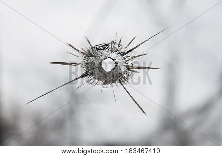 Broken window glass with a bullet hole