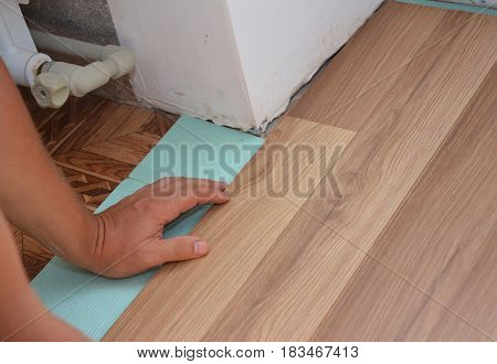Man Installing Laminate Wood Flooring in Problem Area. Worker Installing wooden laminate flooring. Handyman laying down laminate flooring boards while renovating a house.