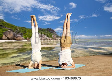 fitness, sport, yoga and people concept - couple making headstand pose on mat over exotic tropical beach background