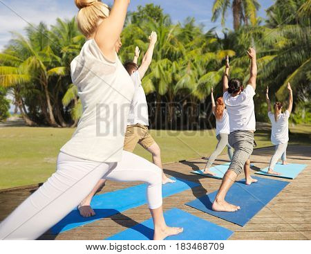fitness, sport, yoga and healthy lifestyle concept - group of people making high lunge or crescent pose over natural background with palm trees