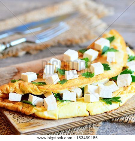 Homemade stuffed omelette. Fried omelette stuffed with tofu cubes and fresh parsley on a wooden board. Cutlery, burlap textile on rustic wooden table. Healthy breakfast omelette idea. Closeup