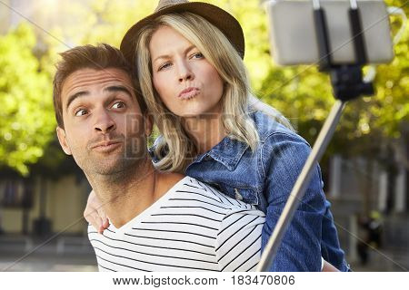 Couple making faces for selfie in city