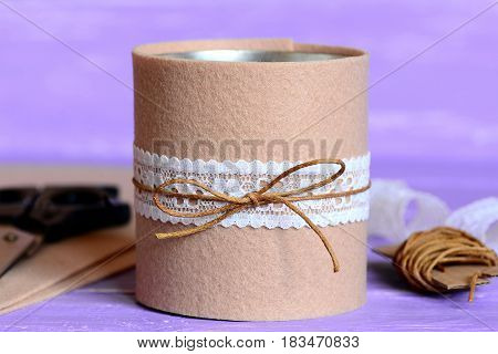 Tin can decorated with beige felt and white lace. Quick, simple and beautiful way for decorating old tin can. Recycled craft projects. Materials for creative work on a lilac wooden table. Closeup