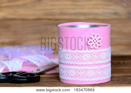 Recycled can, tools and materials on a wooden table. Tin can decorated with pink felt, white lace and flower button. Recycled tin can crafts and projects for home. Closeup