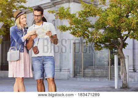 Couple reading map in city - halffigur