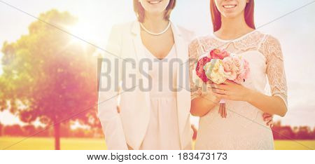 people, homosexuality, same-sex marriage and love concept - close up of happy married lesbian couple with flower bunch over oak tree at summer park background