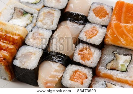 Sushi and rolls closeup background, japanese restaurant delivery. Salmon, unagi, california and other healthy meals