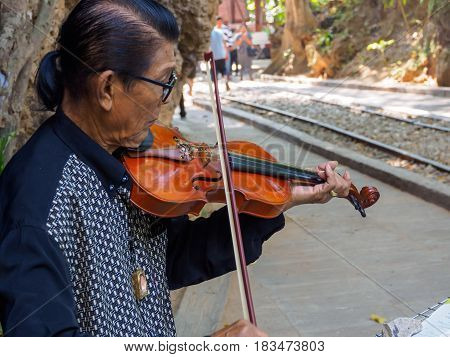 Kanchanaburi Thailand - December 252516 : Asian musician violinist playing violin in public park.