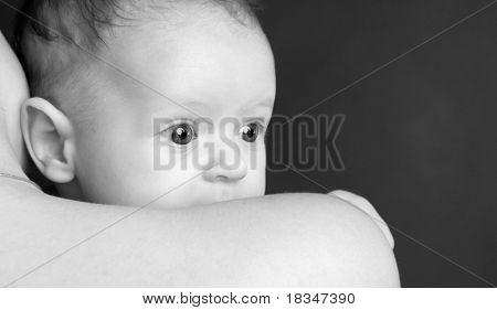 Baby on a mum's shoulder closeup