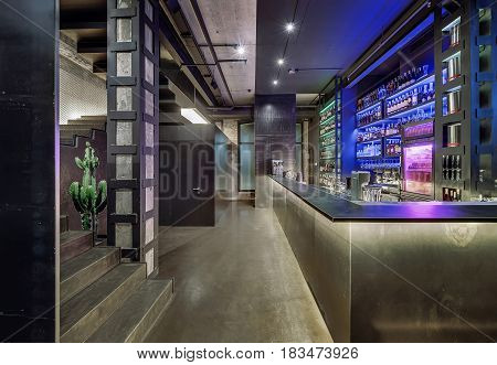 Luminous restaurant in a loft style with brick and concrete walls, column, stairway and a glossy floor. There is a bar rack, shelves with bottles and glasses, fridge, bar equipment, big cactus.