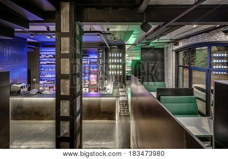 Bar in a loft style with brick and concrete walls, column, glowing lamps and a glossy floor. There is a bar rack, shelves with bottles and glasses, fridge, bar equipment, chairs, tables with sofas.