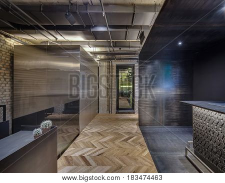 Luminous hall in a loft style cafe with brick and concrete walls and a parquet on the floor. There is a glossy metal cabin with a door, dark textured rack, stand with cactus in the pots, glass door.