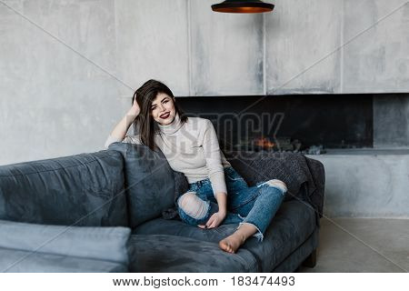 girl sitting on the couch. Room in loft style. Room with a fireplace. The girl with his feet on the couch