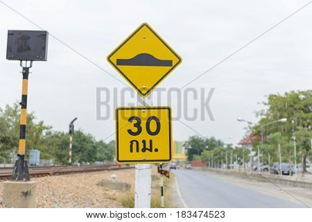 Warning sign of washboard road and Speed limit sign (30km.) in Thai language on the road