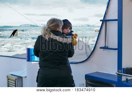 Woman with child on polar trip. In the background pack ice polar bear and a whale.