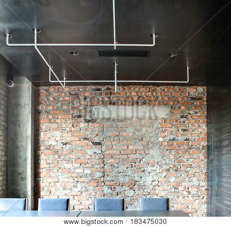 Hall in a loft style in a cafe with brick walls and concrete column. There are tables with chairs, white pipes on the dark ceiling. Horizontal.