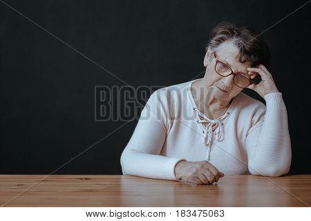 Lonely Senior Sitting Beside Table