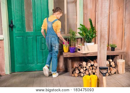 Back View Of Little Girl In Denim Overalls Standing On Porch With Flower Pots