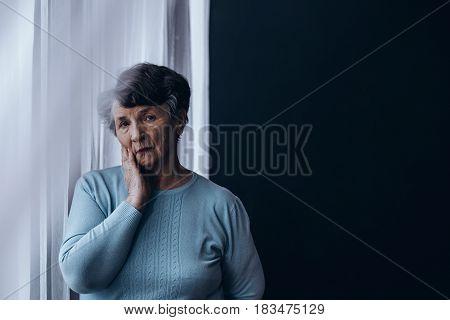 Elderly Woman Standing Beside Window