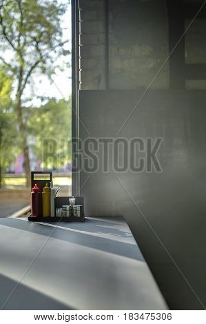 Gray table on the window background in a cafe with brick wall. There are sauces, paper tissues, toothpicks and condiments on the table. Closeup. Vertical.