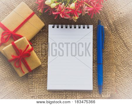 flower bouquet gift and red flower note book and blue pen on brown sack background