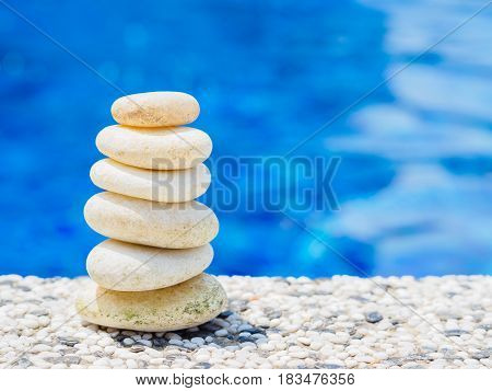 Balance Stones stacked to pyramid in the soft blue water background to Spa ideas design or freedom and stability concept on rocks.