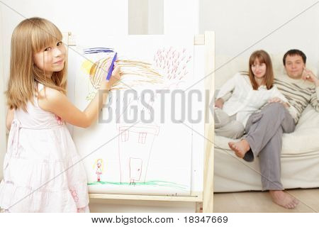 Smiling girl drawing the house