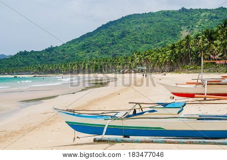 Local boats on Nacpan Beach on sunny day. El Nido, Palawan, Philippines.