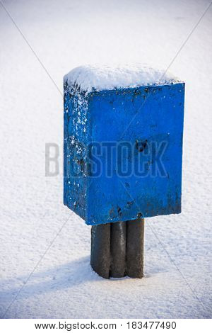 close-up of old blue electric box deep in snow