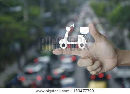 Motor bike icon on finger over blur of rush hour with cars and road Business delivery service concept