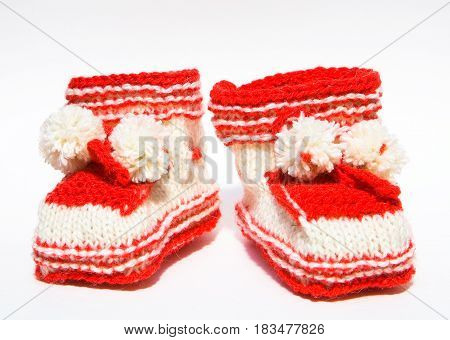 Baby clothes. Red booties with handmade pom-poms.