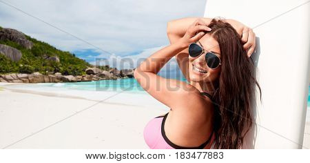summer vacation, travel, surfing, water sport and people concept - young woman in swimsuit with surfboard over exotic tropical beach and ocean background