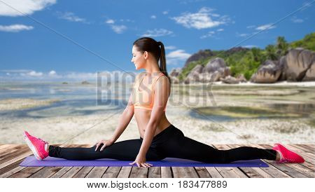 fitness, sport, training, people and exercising concept - smiling woman doing splits on mat outdoors over beach over exotic tropical beach background