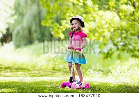 Little Girl Riding A Colorful Scooter