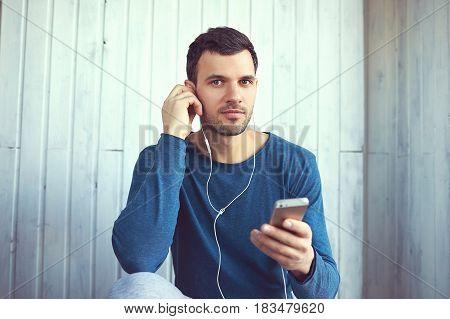 Brown eye guy wearing blue pyjamas is fixing his headphone