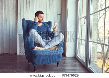 Man is listening to the music through his phone. Guy is sitting in the blue knickted chair