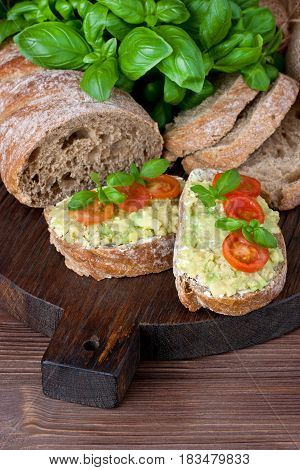 Freshly baked traditional ciabatta bread and avocado cream  on wooden board