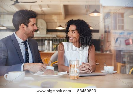 Two Businesspeople Meet In Coffee Shop Shot Through Window