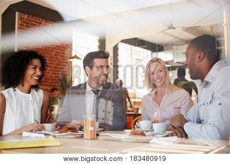 Businesspeople Meeting In Coffee Shop Shot Through Window