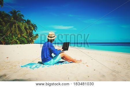 man with laptop on tropical beach, remote work concept