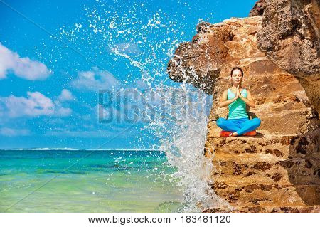 Meditation on sea surf with splashes background. Active woman sit on beach rock and practicing yoga to keep fit and health. Healthy lifestyle fitness training sport activity on summer family holiday