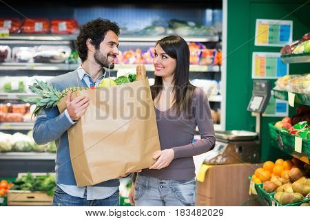 Couple holding a bag full of vegetables in a supermarket